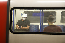 © Licensed to London News Pictures. 15/06/2020. London, UK. Passengers wear face masks as they travel on the underground. New rules allowing some non-essential retail businneses to open and mandatory face masks on public transport have started today. Photo credit: Peter Macdiarmid/LNP