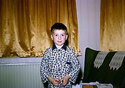 Young boy wearing pyjamas at home looking straight at camera, British culture 1967