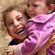 Excited young girl picks up her upset sibling. Dahab Island, Cairo.