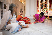 Adu having the edges of both her feet painted with a deep red dye called 'alta'. Wearing alta on the feet has great significance for Hindu women in Bengal and Bangladesh, as the red colour is associated with fertility. This is one of the many ways in which the colour red is worn by Bengali women, along with the red bindi, red sindoor and red-border sari, all of which are symbols of marriage and womanhood.