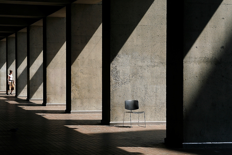 Light filters down onto a stray desk chair and a female student outside Kane Hall on the University of Washington campus in Seattle, Washington.