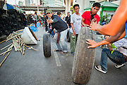 Apr. 30 - BANGKOK, THAILAND: Red Shirts move tires to the new barricade they built in the Sala Daeng intersection in Bangkok Friday. The Red Shirts moved one of their barricades in the Sala Daeng Intersection in Bangkok Friday In one of the first positive moves to take place since the Red Shirts occupied central Bangkok in early April. The barricade was moved far enough back to open one lane of traffic on  Ratchadamri Street to allow ambulance access to King Chulalongkorn Memorial Hospital, a large hospital at the intersection. Many of the patients in the hospital have been moved to other hospitals because a group of Red Shirts entered the hospital Thursday looking for Thai security personnel, who were not in the hospital. The stand off between the Red Shirts and the government enters its third month in May. The Red Shirts continue to call for Thai Prime Minister Abhisit Vejjajiva to step down and dissolve parliament and demand the return of ousted Prime Minister Thaksin Shinawatra.   PHOTO BY JACK KURTZ