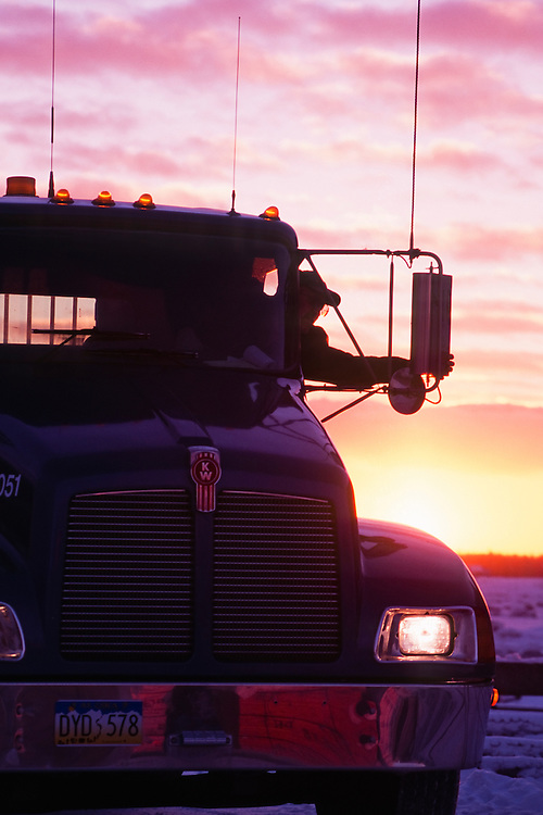 Alaska. Truck driver adjusting rear-view miror on truck with sunset sky in the background.