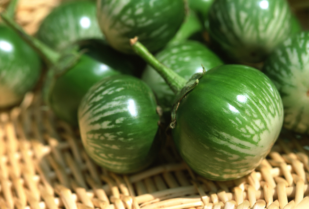 Close up selective focus photograph of a group of Kermit Eggplants on a straw mat