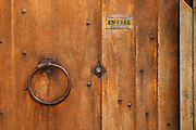 The wooden entrance door with metal ring knocker and old lock, sign saying entree, step in. Chateau Romanin, Saint Remy de Provence, Bouches du Rhone, Provence, France, Europe