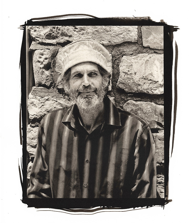A portrait of a man standing against a stone wall in the city of Tzfat in Israel.