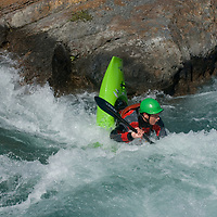 Kayaker Peter Thompson plays in waves on the Kananaskis River in the Canadian Rockies near Calgary, Alberta