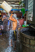 09 JUNE 2014 - YANGON, MYANMAR: A worker rinses off with a water from a communal spigot in the San Pya Fish Market (also spelled Sanpya). San Pya Fish Market in Yangon is one of the largest wholesale fish markets in Yangon. The market is busiest in early in the morning, from before dawn until about 10AM.    PHOTO BY JACK KURTZ