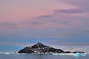 Paulet Island, made of black rock stand out against the pink and lavendar sunrise.
