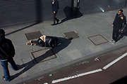 Woman trips and falls over on Lambeth pavement as passers-by walk on. Lying on the pavement, just having landed on the ground, we look down from an aerial perspective to see three men largely ignoring her plight: Londoners being known as aloof and unhelpful to others.  Afterwards, the woman picks herself up and carries on her route unhurt along this stretch of sidewalk in Camberwell, south London.