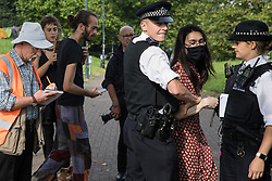 London, UK. 6th September, 2021. Metropolitan Police officers try to prevent a human rights activist from standing in a road in front of a large military vehicle during a protest against the DSEI 2021 arms fair at ExCeL London. The first day of week-long Stop The Arms Fair protests outside the venue for one of the world's largest arms fairs was hosted by activists calling for a ban on UK arms exports to Israel.