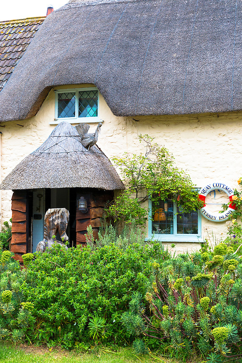 Traditional thatched cottage with leaded light windows at Turkey Island by Porlock Weir in Somerset, United Kingdom