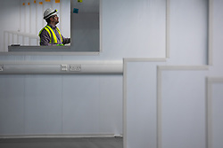 © Licensed to London News Pictures. 10/04/2020. Manchester, UK. A contractor carries out snagging checks on fittings on each of the 648 bays . The National Health Service is building a 648 bed field hospital for the treatment of Covid-19 patients , at the historical railway station terminus which now forms the main hall of the Manchester Central Convention Centre . The facility is due to open next week and will treat patients from across the North West of England , providing them with general medical care and oxygen therapy after discharge from Intensive Care Units . Photo credit: Joel Goodman/LNP