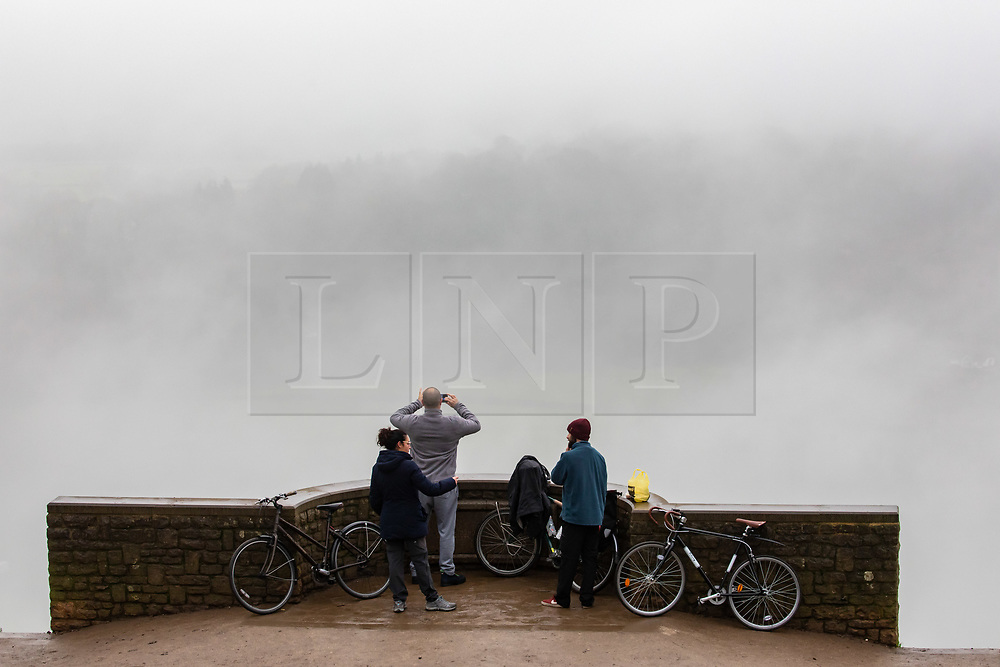 © Licensed to London News Pictures. 07/12/2020. Surrey, UK. Cyclists and walkers stops to enjoy the misty views from the top of Box Hill, Surrey as the Met Office issue a yellow weather warning for freezing fog with disruption to transport for the South East of England today with temperatures near 0c. The Government is expected to rolling out the new Pfizer/BioNTech's coronavirus vaccine tomorrow with reports it has already arrived in the UK for distribution to hospitals around the country. Photo credit: Alex Lentati/LNP