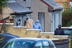 Forensics investigators examine a house near the scene of Sunday evening's quadruple stabbing on Fraser Road, Edmonton in North London and possibly to be linked to a shooting on Gordon Road on Saturday 17th November. Edmonton, London, November 19 2018.