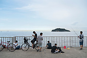 boys fishing and playing with there mobile phone at Umikaze Park in Yokosuka
