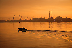 A small boat travels through the Suez Canal at daybreak, with Port Fouad in the distance, in Port Said, Egypt on April 9, 2008. The Suez Canal is one of the most important shipping routes in the world, as it allows two-way water transportation - most importantly between Europe and Asia without the circumnavigation of Africa.