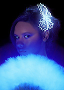 Young girl with glowing fan and glowing butterfly hairpiece.Black light