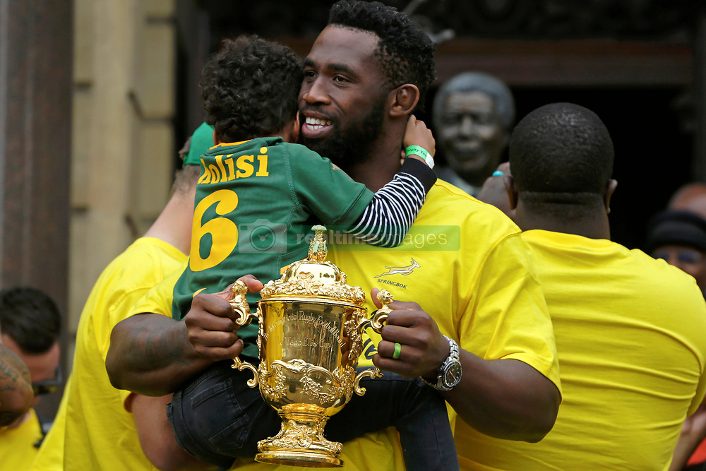 Monday 11th November 2019.<br /> City Hall, Grand Parade,<br /> And City Centre, Cape Town,<br /> Western Cape,<br /> South Africa.<br /> <br /> SPRINGBOKS CELEBRATE WINNING THE RUGBY WORLD CUP CHAMPIONSHIP IN 2019 WITH A COUNTRYWIDE VICTORY TOUR!<br /> <br /> SPRINGBOKS RUGBY WORLD CUP VICTORY TOUR CAPE TOWN!<br /> <br /> The Springboks take the stage outside the City Hall as they are cheered on by thousands of excited fans. South African Captain Siya Kolisi (centre) shares a moment with his son as he holds the Web Ellis Cup.<br /> <br /> The reigning Rugby World Cup Champions namely the South African Springbok Rugby Team, celebrates winning the Webb Ellis Cup during the International Rugby Football Board Rugby World Cup Championship held in Japan in 2019 with their Victory Tour that culminated in the final city tour taking place in Cape Town. Thousands of South African fans filled the streets of the city all trying their best to show their support for their beloved Springboks and to celebrate them winning the Rugby World Cup for the third time. South Africa previously won the Rugby World Cup in 1995, 2007 and now again in 2019. South African Springbok Captan Siya Kolisi took the opportunity to speak to the gathered crowd about how something like this brings unity and that we should live together as a nation that practices what is known as ubuntu. Ubuntu is a quality that includes the essential human virtues of compassion and humanity. This image taken in Cape Town on Monday 11th November 2019.<br /> <br /> This image is the property of Seven Bang Media Group (Pty) Ltd, hereinafter referred to as SBM.<br /> <br /> Picture By: SBM / Mark Wessels. (11/11/2019).<br /> +27 (0)61 547 2729<br /> mark@sevenbang.com<br /> www.sevnbang.com<br /> <br /> Copyright © SBM. All Rights Reserved.
