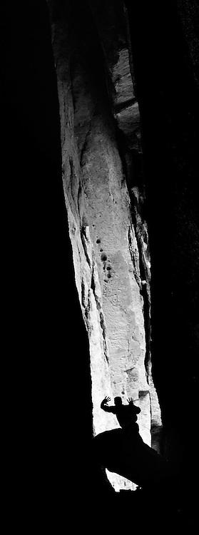Hiker silhouetted in a cave, Bruneau - Jarbidge Rivers Wilderness, Idaho.
