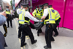 © Licensed to London News Pictures. 03/09/2020. London, UK. Police officer arrest an Animal Rebellion protester after they fixed themselves to an abandoned truck outside the Department of health in Victoria St.  The protesters have fixed themselves outside and inside the truck. Photo credit: Ray Tang/LNP