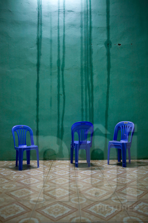 Blue plastic chairs are placed close to a green wall. Water streaks appear on the concrete. Vietnam, Asia.