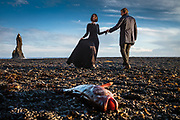 Vik i Myrdal, Iceland, 1 apr 2019, Sunset at Reynisfjara black sand beach. Couple acting for a fashionshoot in between the death fish