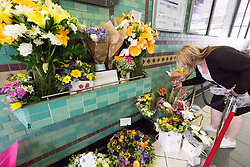 © Licensed to London News Pictures. 07/07/2015. London, UK. A woman lays flowers shortly before people observe a minute silence at Aldgate tube station in London, on the tenth anniversary, for victims of the 7/7 bombings. Photo credit : Vickie Flores/LNP