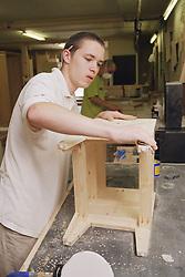Cabinet maker sanding down bedside cabinet using sand paper,