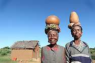 Behony, 60, from left, and Rania, show the traditional way of carrying water in gourds in the Malagasy community of Beteny which benefited from two water points and a treadle pump installed by CRS with USAID/OFDA funding. The women used to walk an average of 4-6 kilometers a day to collect water for their families daily use.  They would irrigate their small garden plot by digging water out of the sand at the dried out Imanda River and carry it in gourds to water their plants. The treadle pump has made their job significantly easier.  What once took six hours out of their day can now be accomplished in 2 1/2 hours. They've also noticed that their crops are much heartier and are able to harvest monthly whereas before they harvested every other month.  Seeds provided as part of the project have helped them diversify their food baskets. The mothers say that that the rope pump water points in the village coupled with the installation of latrines, tippy taps, and hygiene classes, have caused a significant drop in diarrhea cases among the children.  Another benefit they've seen is that they can now use the water to make quick repairs to their homes, what once took 10 days in water collection and mud preparation can be accomplished in 4 days.