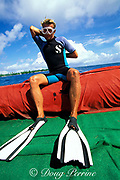 divemaster Jean-Jacques Gandy prepares<br /> to dive, still wearing fins with bite from<br /> gray reef shark, Rangiroa Atoll, Tuamotu<br /> Islands, French Polynesia ( South Pacific Ocean )