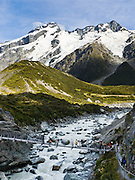 Hike under Mount Sefton on Hooker Valley Track swing bridge, Aoraki / Mount Cook National Park, South Island, New Zealand. In 1990, UNESCO honored Te Wahipounamu - South West New Zealand as a World Heritage Area.