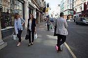 Man with a pink leg cast on New Bond Street, London, UK.