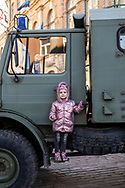Tallinn, Estonia - February 24, 2020: Milana, age 4, poses on a military truck parked near Freedom Square during Estonian Independence Day celebrations.