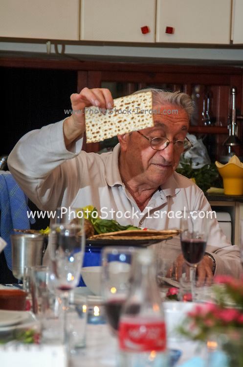 master of ceremony conducting the service around the Traditional sedder table set for a Jewish Festive meal on Passover