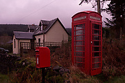 A remote public phone kiosk and post box near a cottage home at Pennyghael, Isle of Mull, Scotland. It is early morning as the light still has a pink tint during winter in the Inner Hebrides. Mobile (cell) phone signals are still weak in this area of Scotland so the phone box is used by locals and the many visitors who come this way en route to the Holy Isle of Iona.