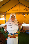 """Maroofa Rashid, 10, whose family was affected by the floods, holds up a sign with the message """"I can play here in the Child-Friendly Space"""" in Purnishadashah village, Jammu and Kashmir, India, on 24th March 2015. Save the Children has set up Child-Friendly Spaces (CFS) in many of the affected villages, providing a tented area where children can take emotional shelter and receive psychological first aid as well as continue their education as their homes and schools are being rebuild. Photo by Suzanne Lee for Save the Children"""