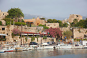 Byblos Castle and restaurants surround yachts and fishing boats moored in the marina at Byblos, Lebanon