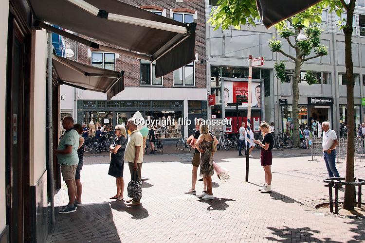 Nederland, Nijmegen, 30-5-2020 Per i juni gaan nieuwe en versoepelde maatregelen in zoals de opening van horeca en terrassen .Terrassen zijn nu nog gesloten . Stadsbeeld van een winkelstraat in het centrum van de stad . Nu de drukte toeneemt vanwege het mooie weer en het langdurige thuisblijven, binnenzitten, is het straatbeeld drukker . Mensen zijn aan het winkelen en staan in de rij in de openlucht om hun beurt af te wachten . Winkels hebben desinfectiegel ter desinfectie van de handen bij de ingang staan .Foto: Flip Franssen