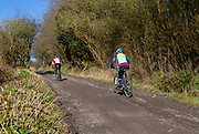Two people cycling up a track, Cherhill, Wiltshire, England, UK