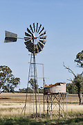 Windmill and rusted water tank in farm paddock in rural country Alectown, New South Wales, Australia. <br /> <br /> Editions:- Open Edition Print / Stock Image