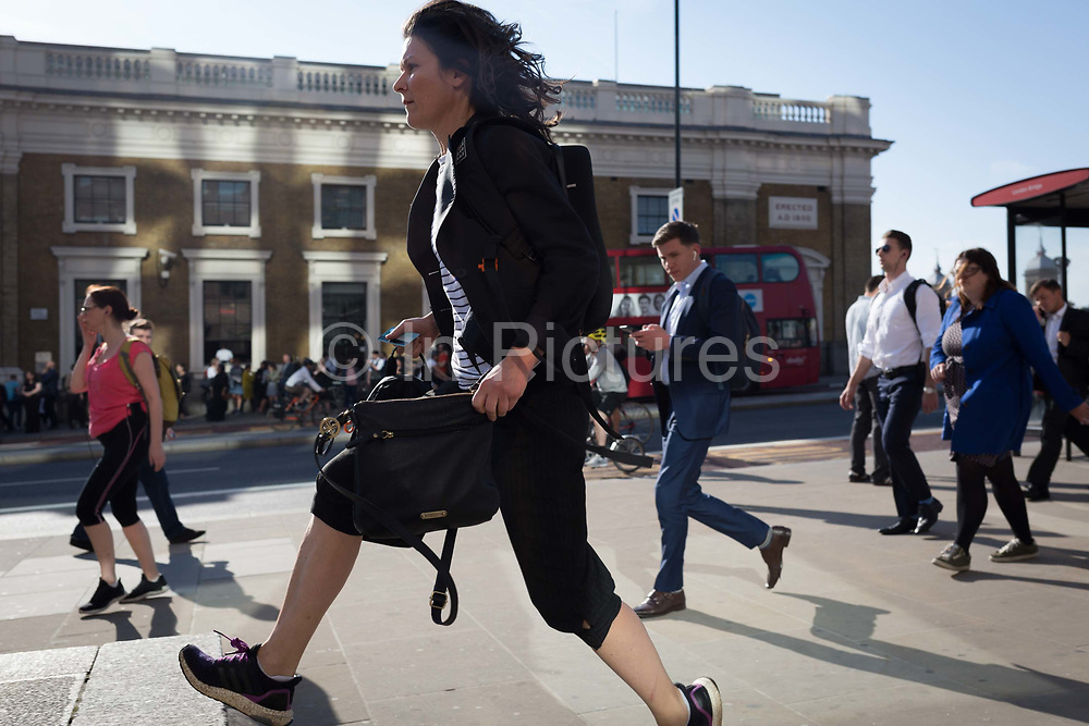 Commuters and other pedestrians walk over London Bridge, the oldest of the capitals crossing over the river Thames between the capitals financial district, the City of London, and Southwark on the south bank, on 15th May 2018, in London, UK.