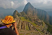 A tourist is admiring the lost Inca city of Machu Picchu. Now it is one of the new seven wonder of the modern world. It is located in Cusco, Peru