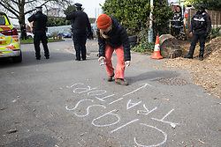 Sipson, UK. 8th March, 2021. A woman writes the words 'Class Traitors' in chalk on the road during an operation by bailiffs from the National Eviction Team (NET) and the Metropolitan Police to evict residents from the remaining section of a squatted off-grid eco-community garden known as Grow Heathrow. Grow Heathrow was founded in 2010 on a previously derelict site close to Heathrow airport in protest against government plans for a third runway and has since made a significant educational and spiritual contribution to life in the Heathrow villages which are threatened by airport expansion.