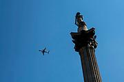 An aeroplane passes Nelsons Column, Trafalgar Square, London.