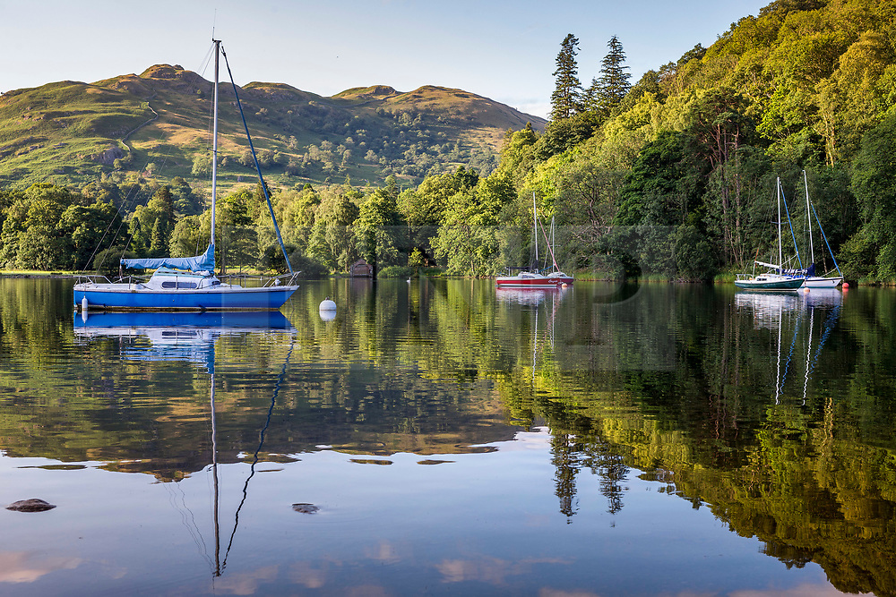 © Licensed to London News Pictures. 03/08/2020. Glenridding UK. Boats reflect into the calm waters of Ullswater lake in Glenridding this morning in Cumbria. Photo credit: Andrew McCaren/LNP