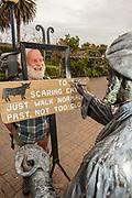 Botanist and Hinewai Reserve manager Hugh Wilson has famous Akaroa artist touch up sign before Banks Peninsula Walk, Akaroa