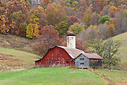 A barn and silo grace a field amidst fall leaf colors in West Virginia, USA.
