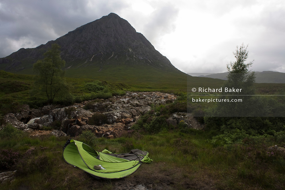 Abandoned Quechua tent and Stob Dearg mountain with rocky River Coupall amid magical scenery in Glencoe, Scotland
