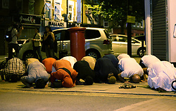 """Local people observe prayers at Finsbury Park in north London, where one person has been arrested after a vehicle struck pedestrians, leaving """"a number of casualties""""."""